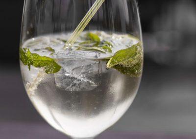 Hugo-Drink mit Eiswürfel, Minzblättern und Strohhalm